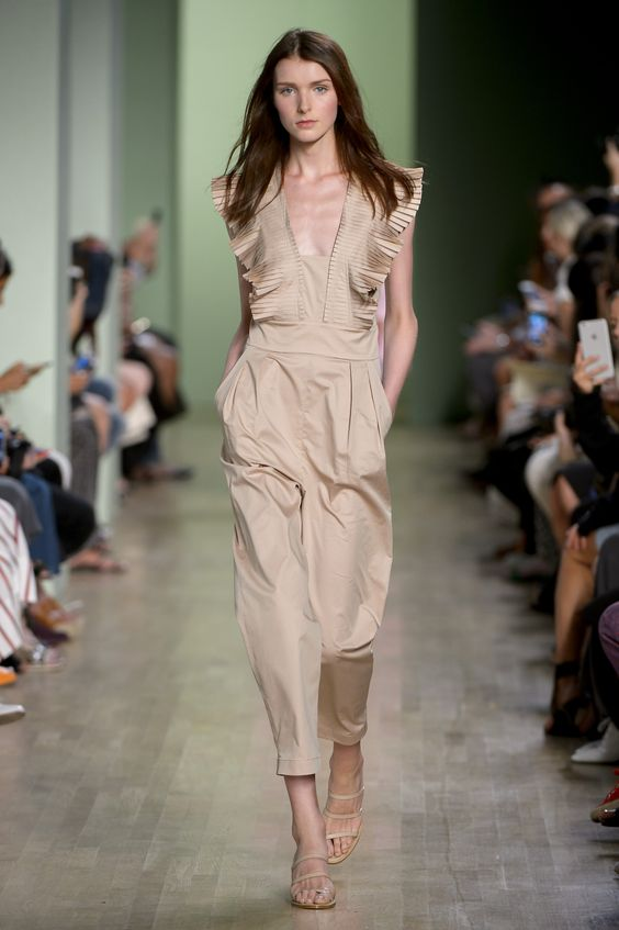 The model in a jumpsuit with pleated ruffle detailing.