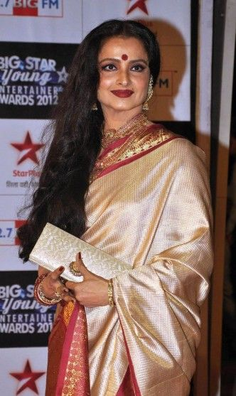 Rekha in kanjivaram saree with red border.