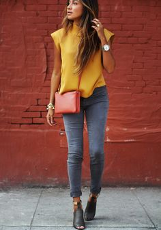 Mustard colored shirt paired with dark grey jeans and black heels