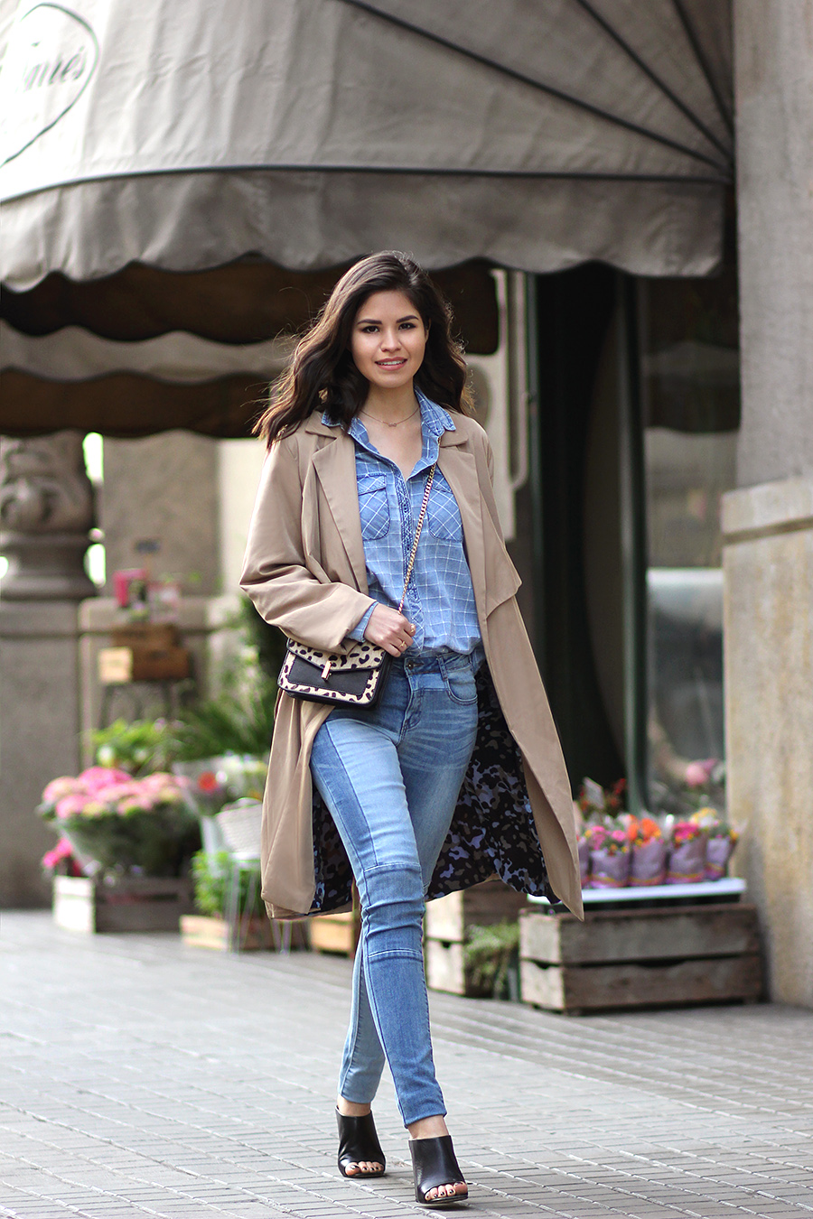 The model in double denim skinny jeans with mules and coat.