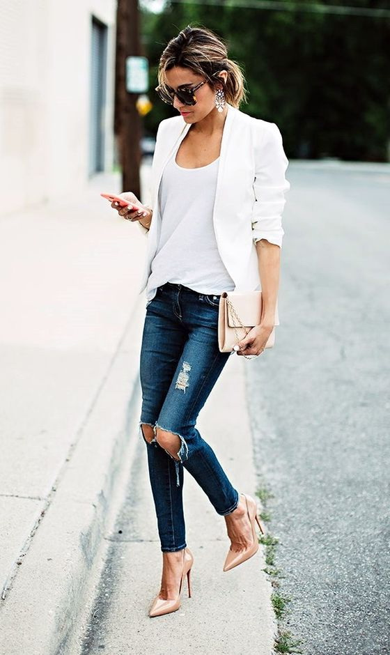 The model in white blazer with cuffed sleeves tucked in knee-ripped skinny jeans.