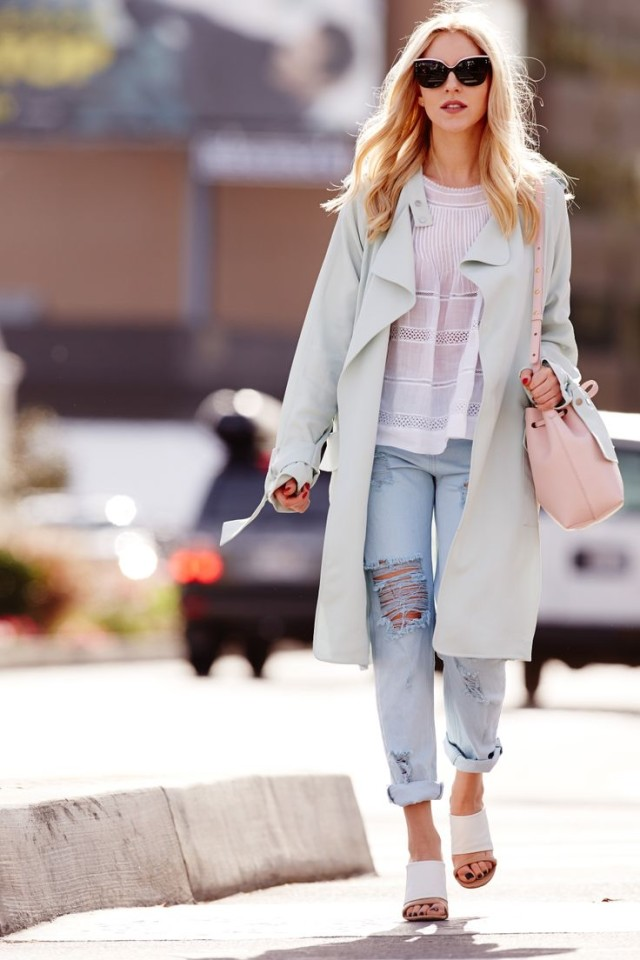 The model in duster coat, white top with rolled boyfriend jeans.