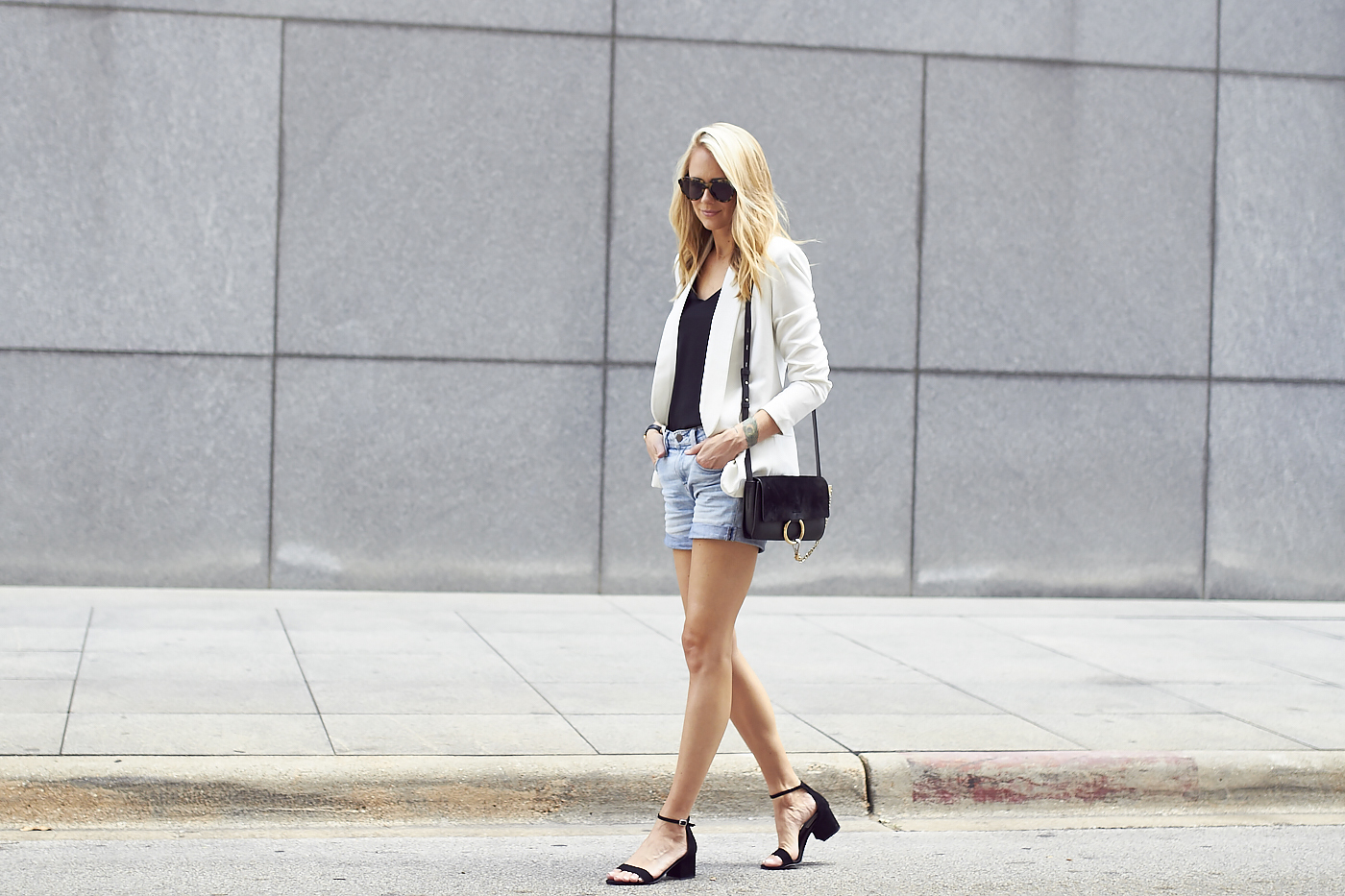 The model in White blazer with denim shorts and handbag for chic summer outfit.