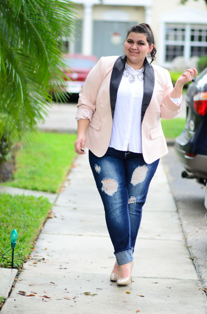 The model in plus size outfit with pink blazer, white shirt and ripped jeans.
