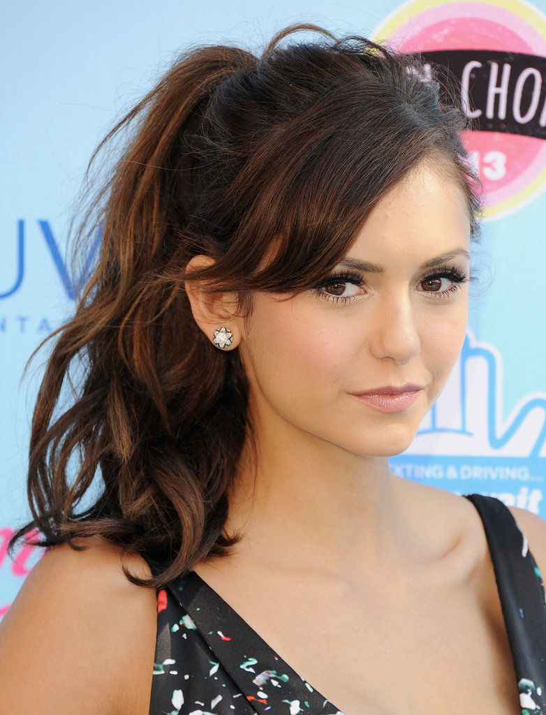 Nina Dobrev's messy ponytail and side-swept bangs.
