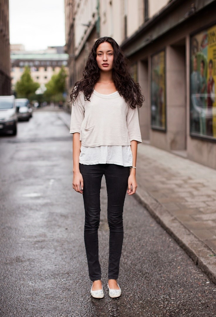 The model in simple tee, skinny jeans and ballet flats.