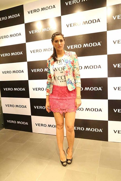 Actress Nargis Fakhri in a bright pink crochet short skirt with a top and well-fitted floral jacket.