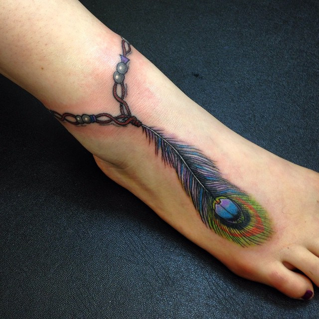 Peacock Feather Tattoo on a woman's leg.