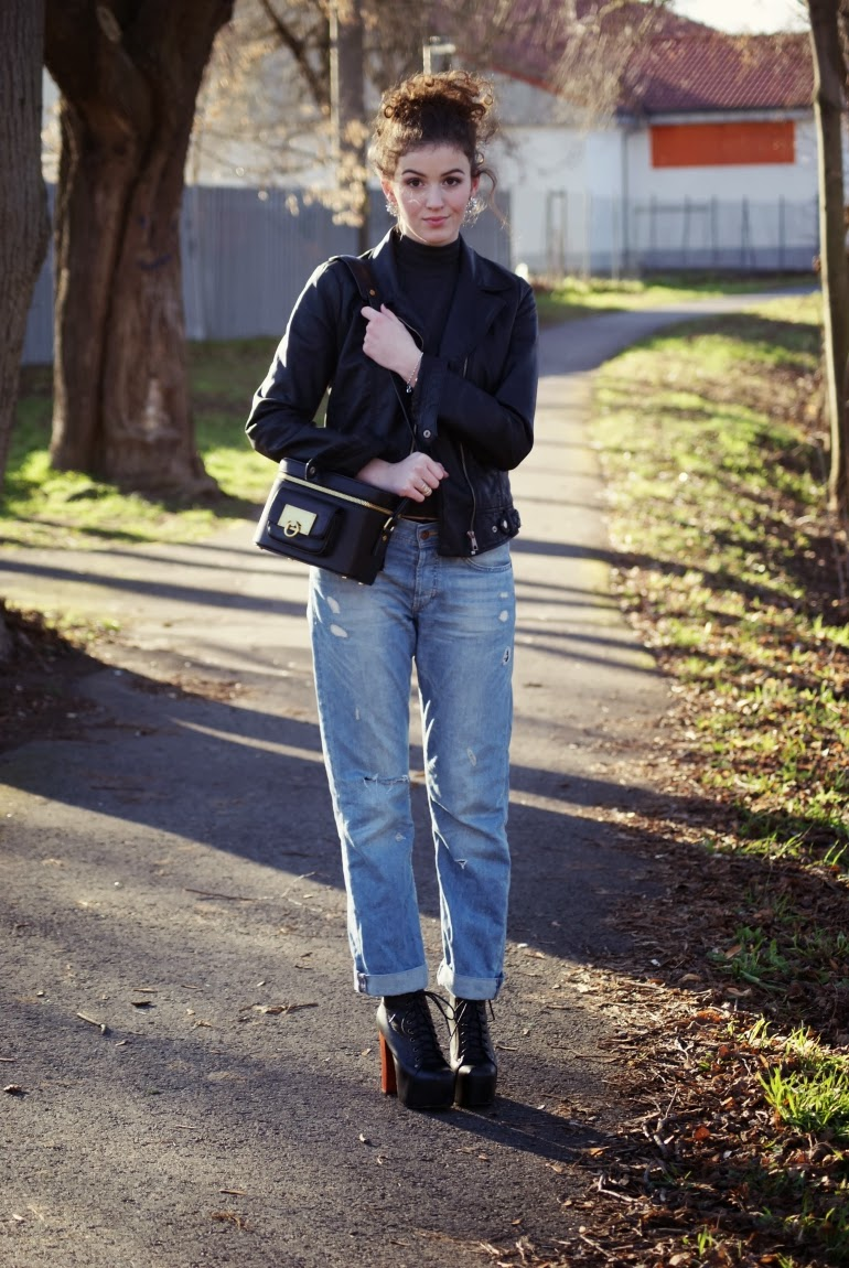 The model in sweater, black jacket and boyfriend jeans.