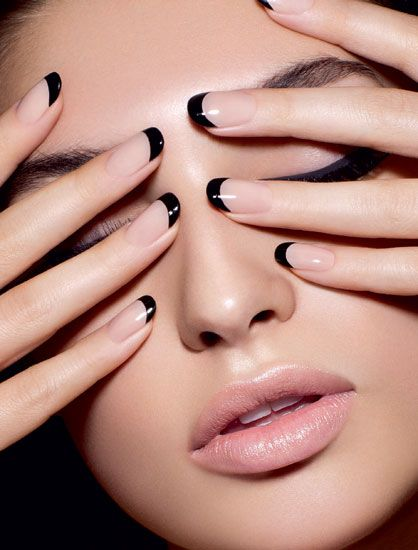 Closeup woman face with Black and Pastel pink nails near eyes.